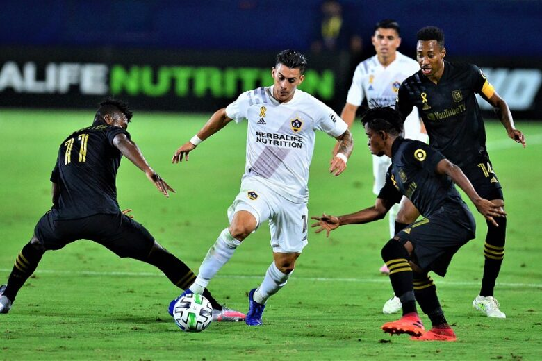 Sep 6, 2020; Carson, California, USA; Los Angeles Galaxy forward Cristian Pavon (10) moves the ball against Los Angeles FC midfielder Jose Cifuentes (11) forward Latif Blessing (7) and midfielder Mark-Anthony Kaye (14)  during the first half at Dignity Health Sports Park. Mandatory Credit: Gary A. Vasquez-USA TODAY Sports